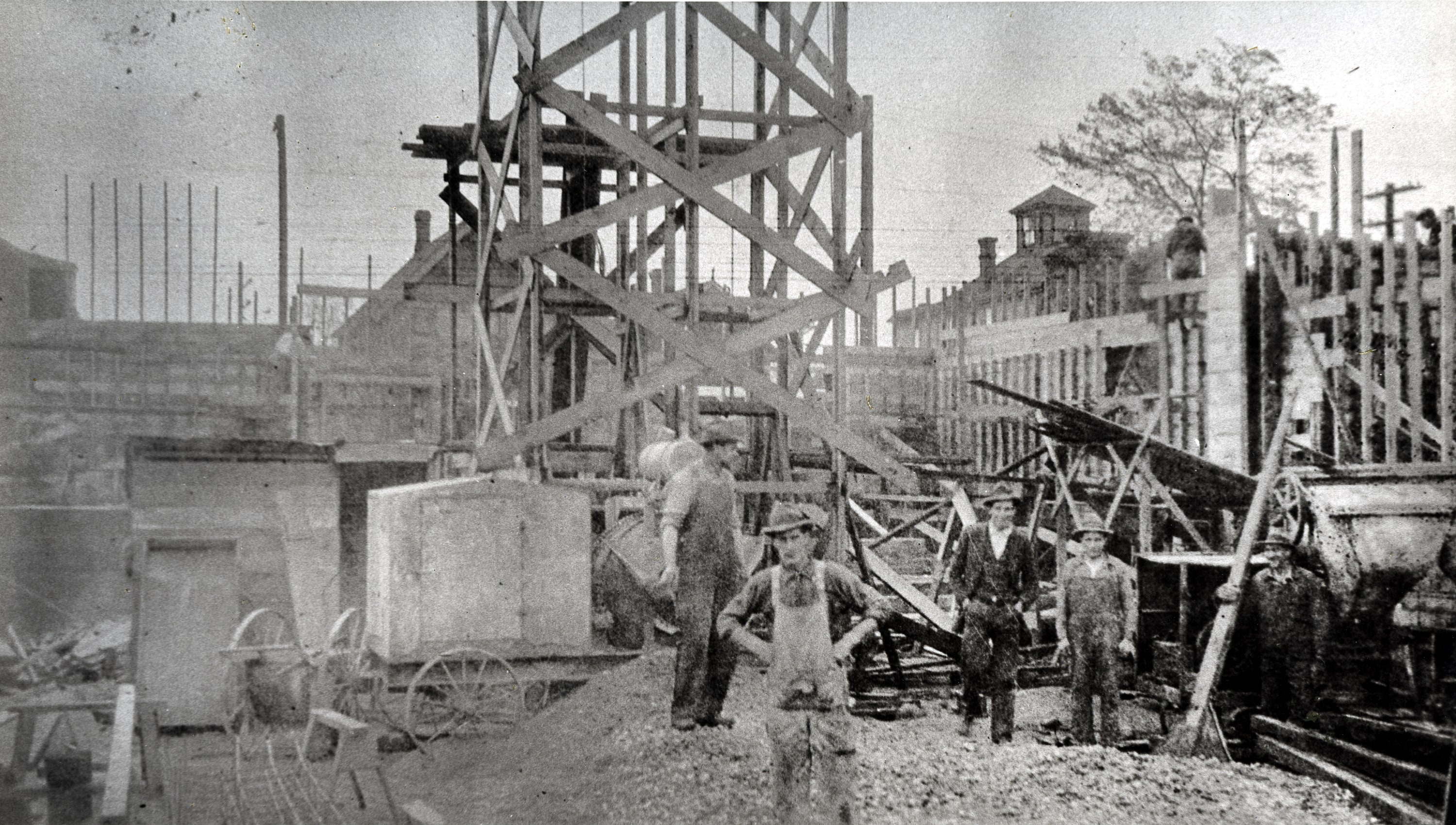 "In this archival photo, five men working at the construction site of the ""new"" school building briefly stop to pose together."