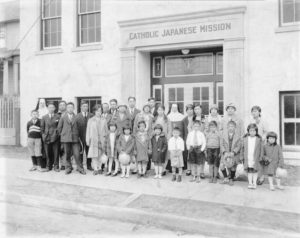 Shown is a photo of a group in front of Catholic Japanese Mission. Two nuns stand behind a group of about two dozen Japanese men, women, and children.
