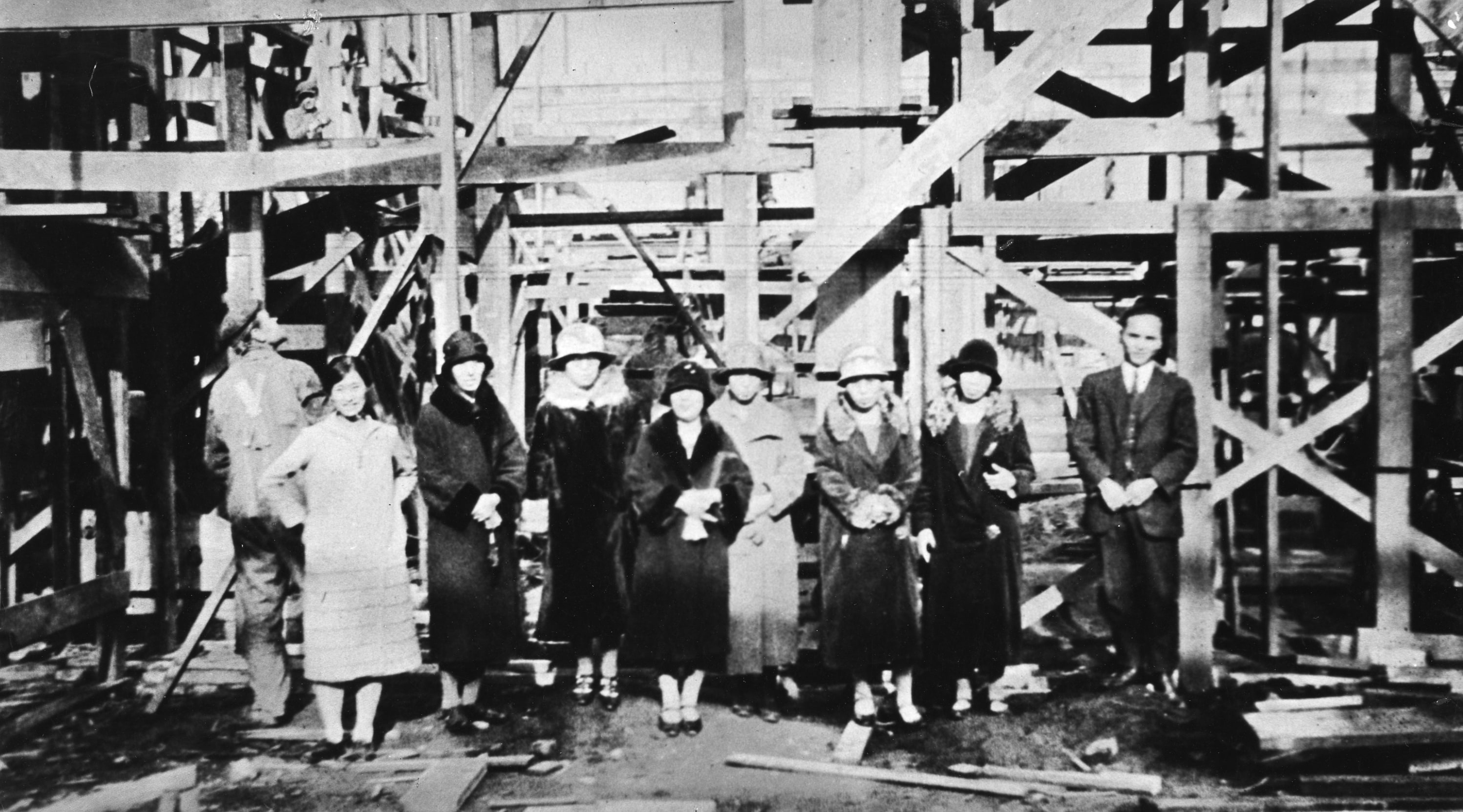 In this photo, Nikkei women and a man pose for a photo in front of a scaffolding. The woman at far left is Hanako Sato, and man on the far right in Tsutae, her husband.