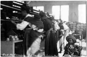 This photo depicts Japanese women in a Steveston cannery working with babies on their backs. A child sits in a stroller to the right of the women, looking at the camera.