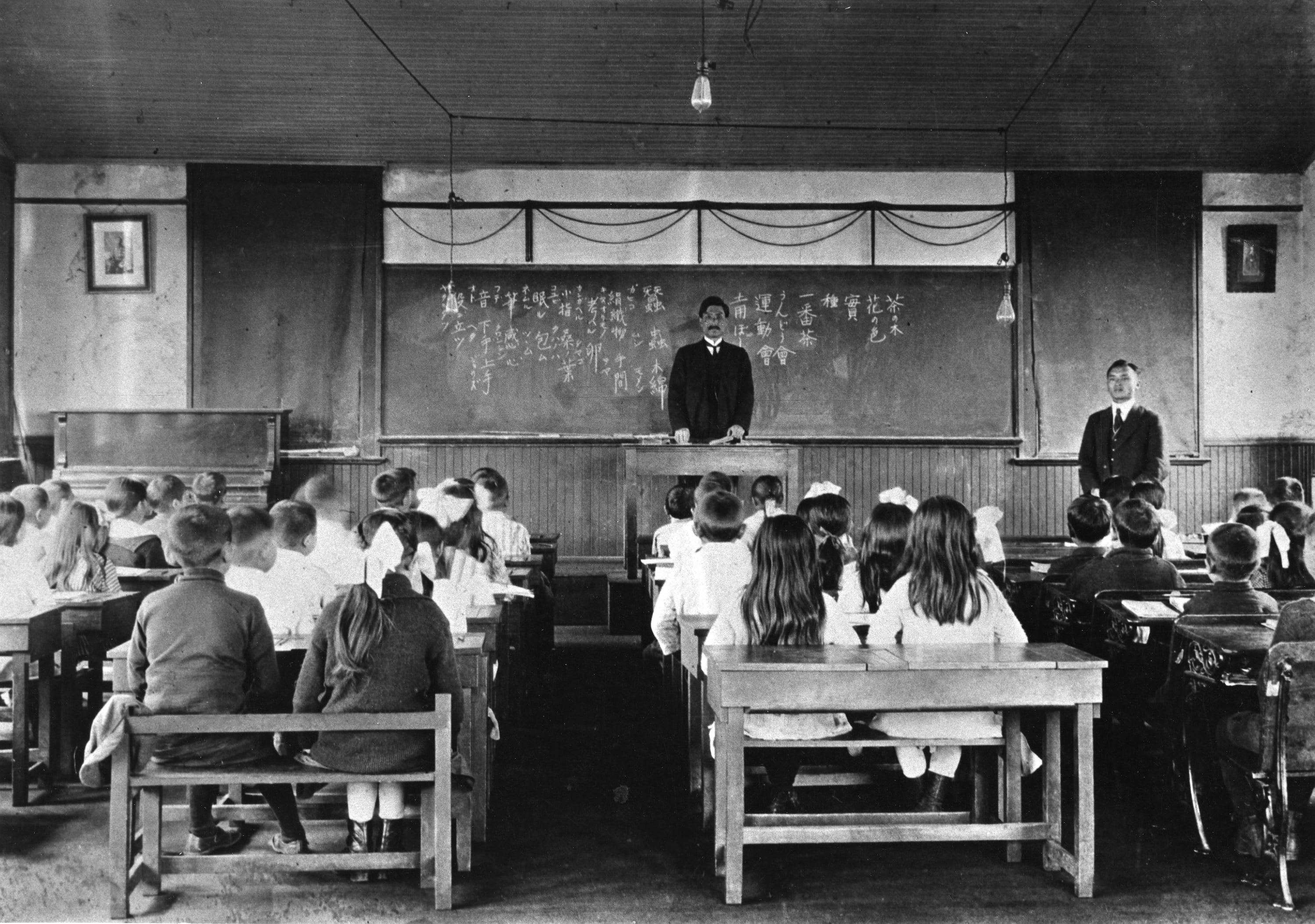 This archival photo shows a Japanese language school classroom in the 1920s. The photo is taken from the back of the class. The pupils have their backs to the camera as they face the teacher standing in front of the class.