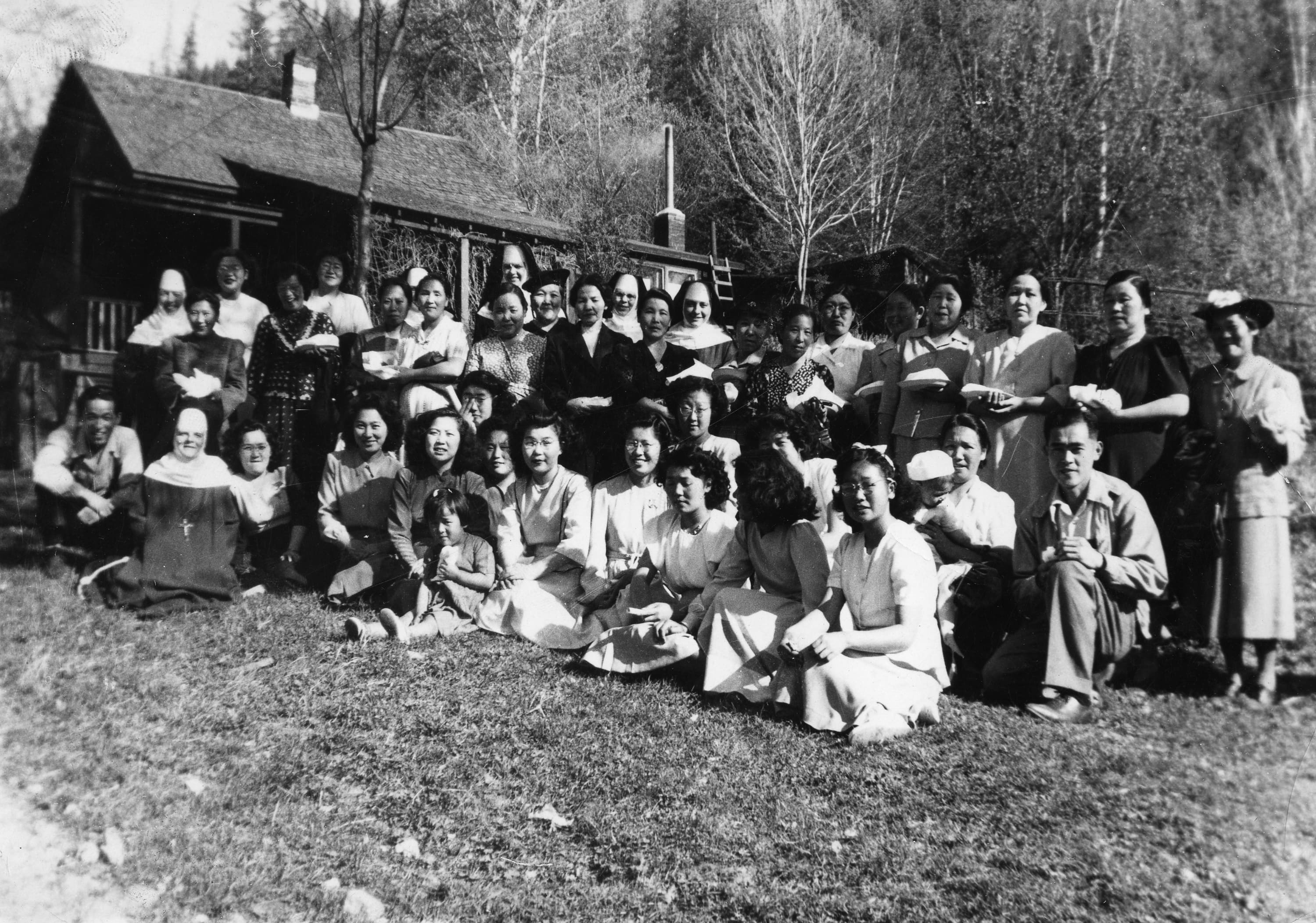This historical photo depicts Nikkei youths, women, and men, along with Catholic Sisters standing and sitting outside a cabin in Greenwood, British Columbia.
