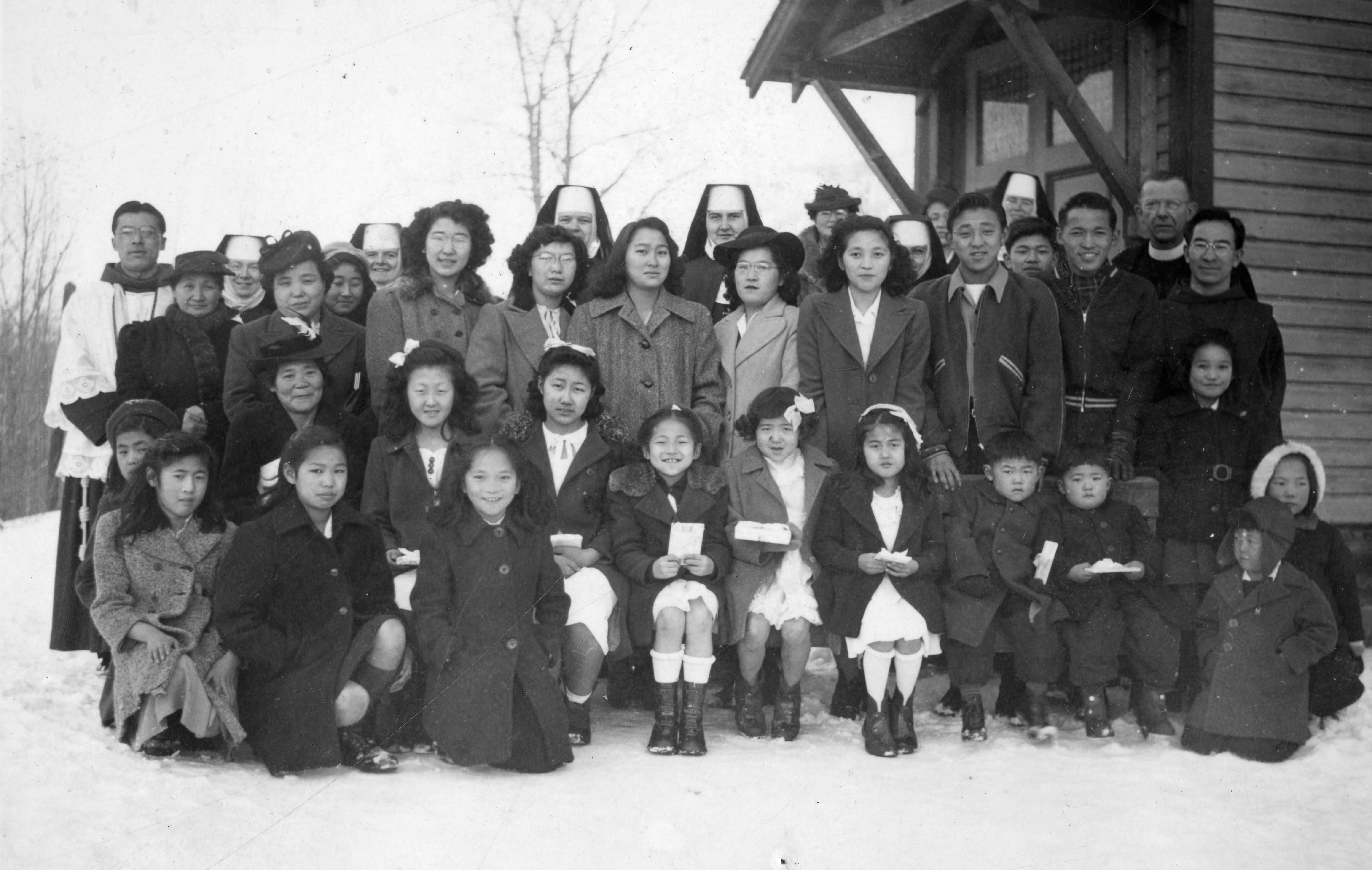 This 1946 photo depicts Japanese children, youths, women and men posing on snow for a photo with Sisters and Priests in Greenwood.