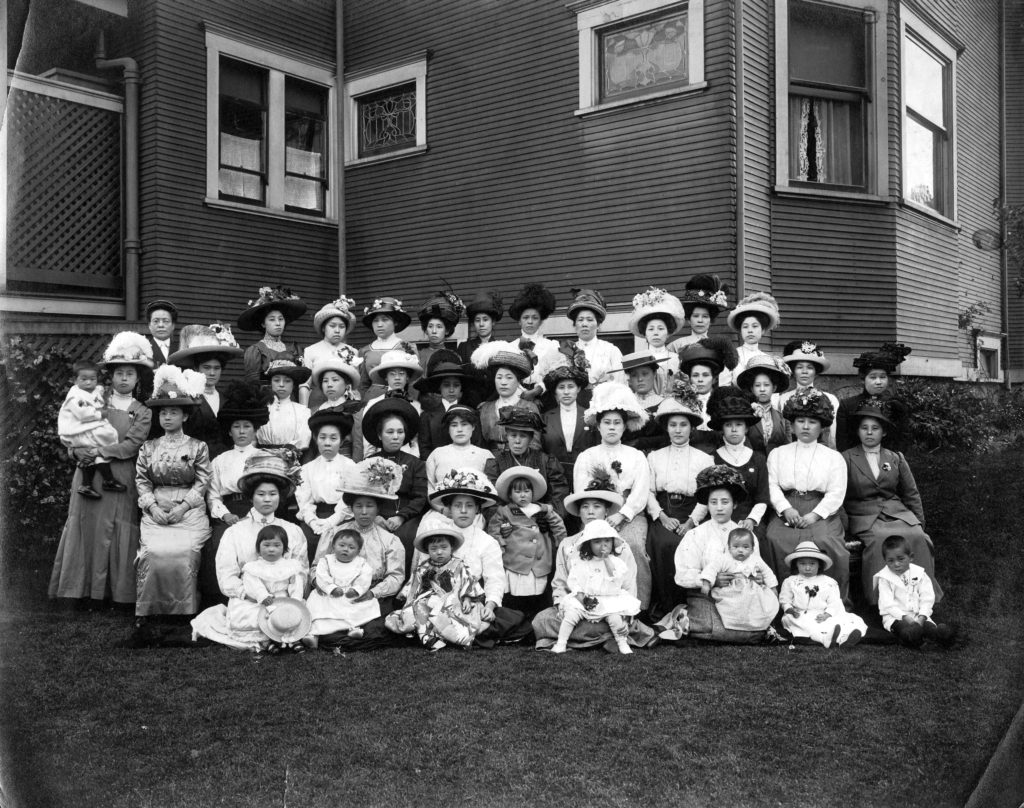 This is a group photo of the Japanese Women's Association from around 1910. The women in the photo wear fine dresses and fancy hats with flowers, which suggests that prominent women took part in this association.