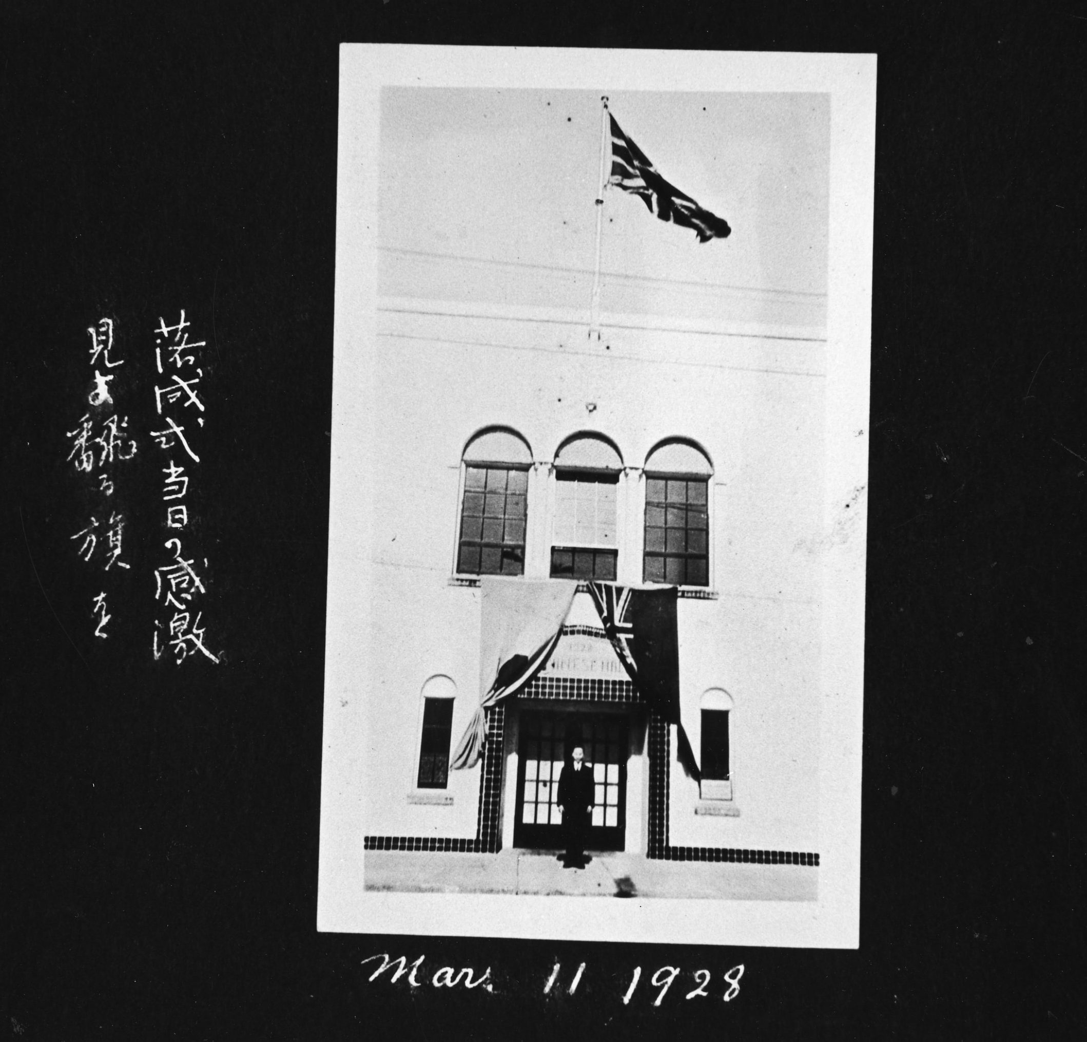 "This image depicts Tsutae Sato standing at the doors of the school on Opening Day. The Japanese caption to the left of the photo says, ""jubilation of the opening day, look at the soaring flag!"""