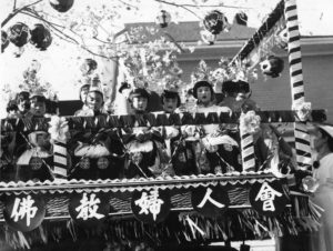 A photo of Buddhist Women's Association-sponsored festival float. Children are sitting on the float, which is topped by a cherry blossom tree and paper lamps.