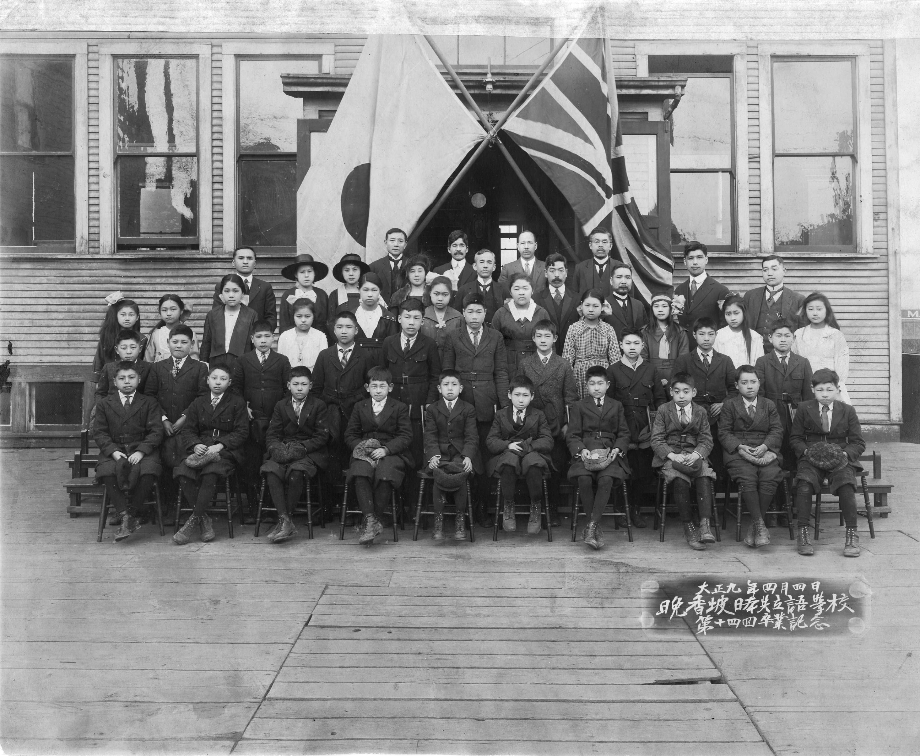 This is a group photo of the Language School's Class of 1920. The school, along with crossed Japanese and British flags, is the backdrop for the photo.