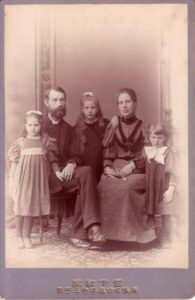 This is a portrait dating to the late 1890s, of John Cooper Robinson, his wife Bessie, and his young daughters. Robinson and Bessie are seated, while the three daughters stand next to them.