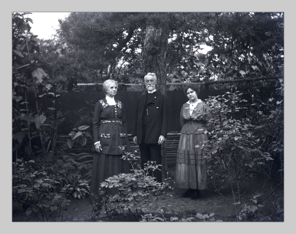 In this photo, Bessie Robinson, John Cooper Robinson, and a young adult Hilda Robinson stand for a photo in a backyard garden.
