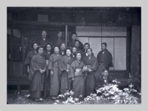 In the photo, a group of fifteen Japanese men and women pose outside a house.