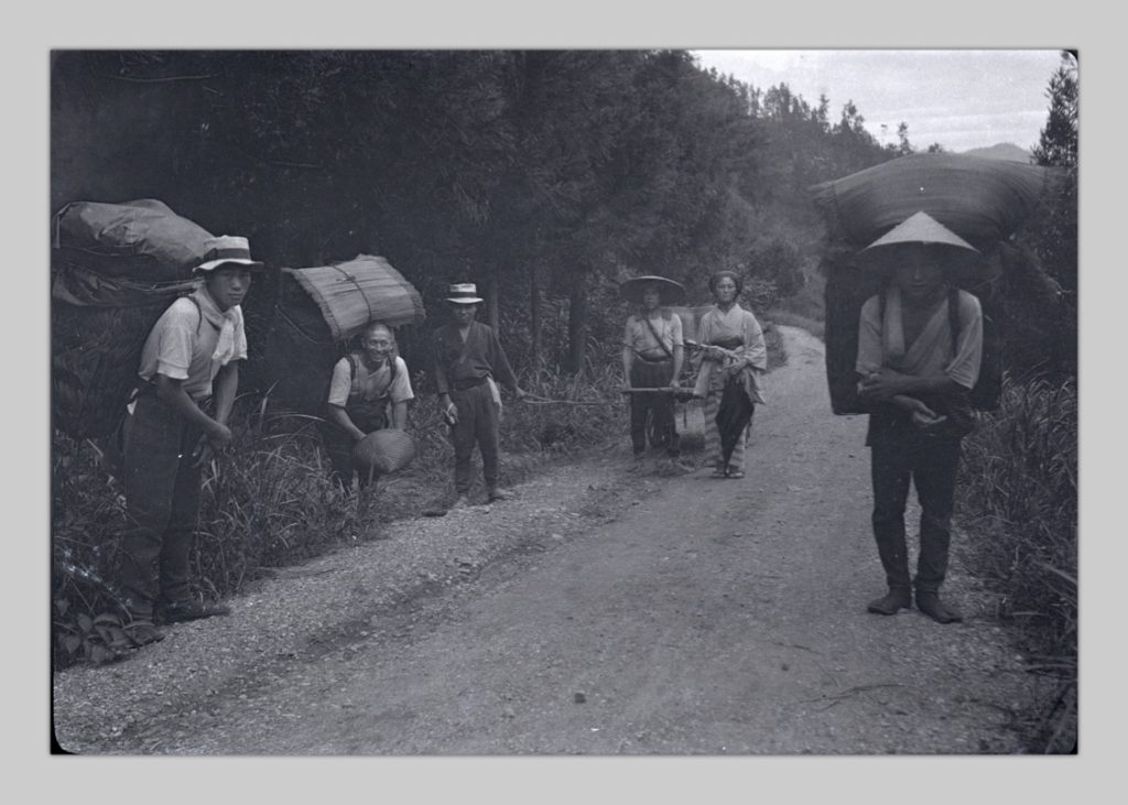 This is a photo, taken by John Cooper Robinson, of villagers carrying large rucksacks on their backs up a dirt-and-gravel road.