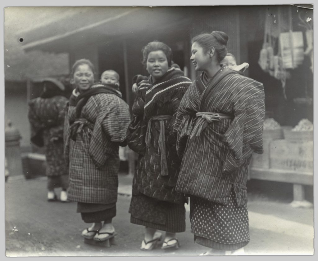 In this photo, three young women stand outside a market chatting. Their babies are swaddled in fabric, which is strapped securely to the mothers' outfits.