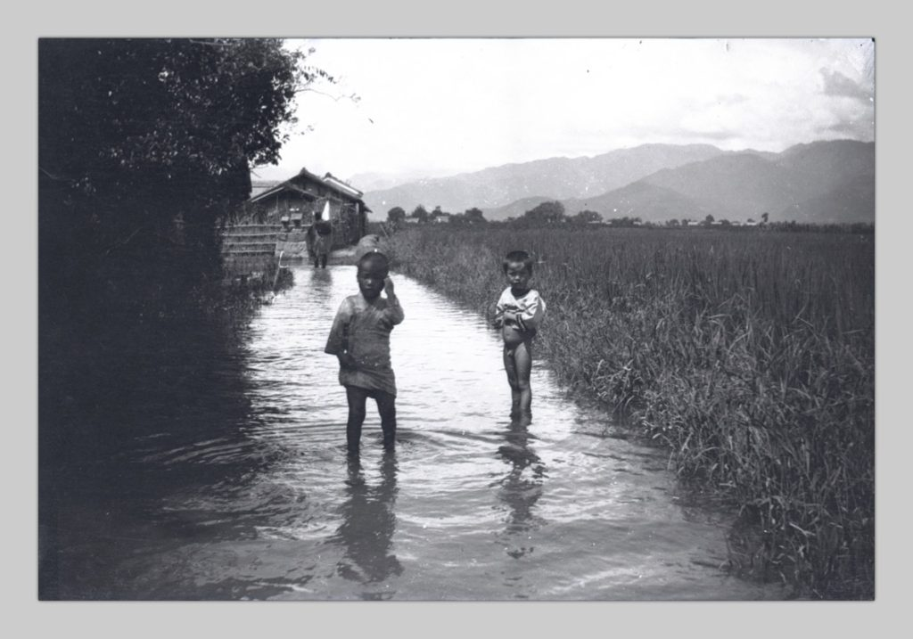 In this photo taken by John Cooper Robinson, two Japanese children stand in the ankle-deep water of an irrigation canal.