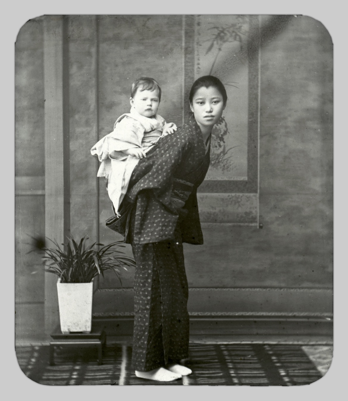 In this photo, one of John Cooper Robinson's young Japanese colleagues, O Ei, poses for a portrait with a 10-month-old Lucy Winifred Robinson on her back.