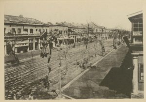 A photo of what appears to be the same empty street depicted in Figure 4, but taken from the vantage point of a balcony along the street.