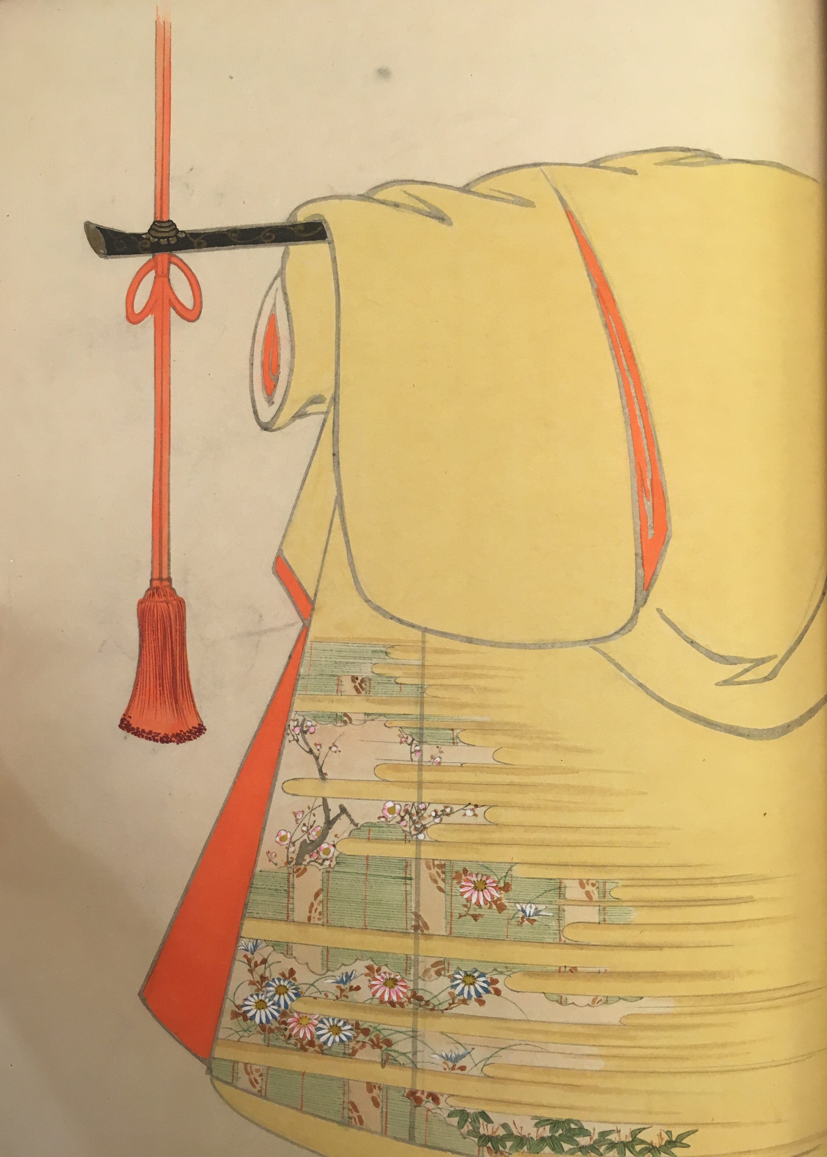 A design of a yellow kimono with red-orange interior. The pattern in the lower corner depicts plums and chrysanthemums partially obscured by a haze.
