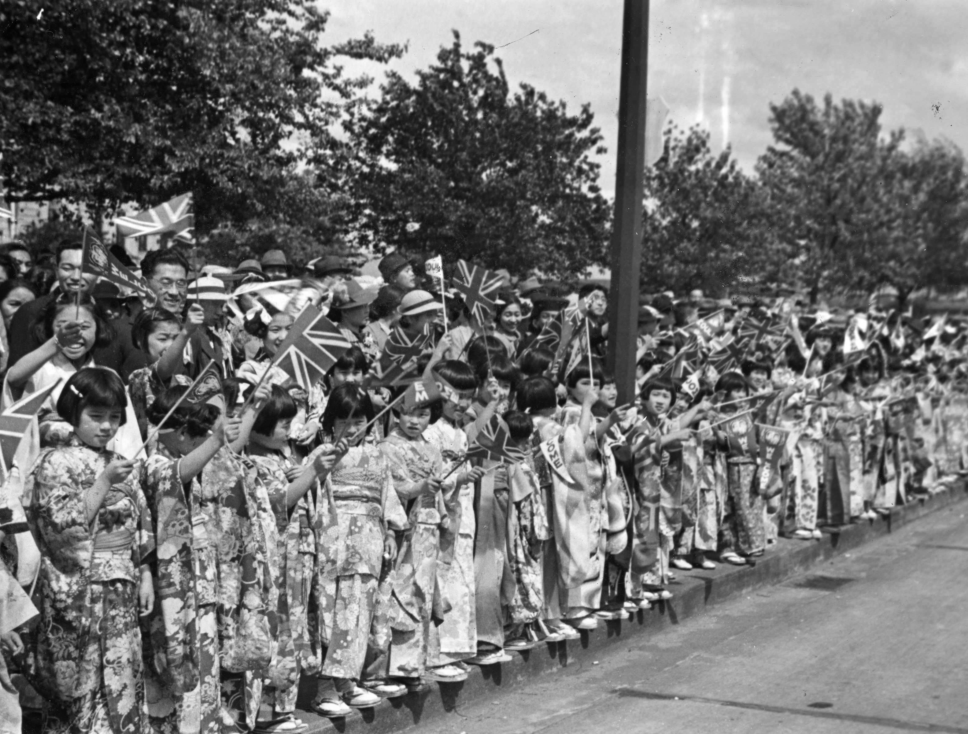 In this photo, rows of girls and young women in kimono along a street wave the Union Jack as the Royal entourage comes their way.