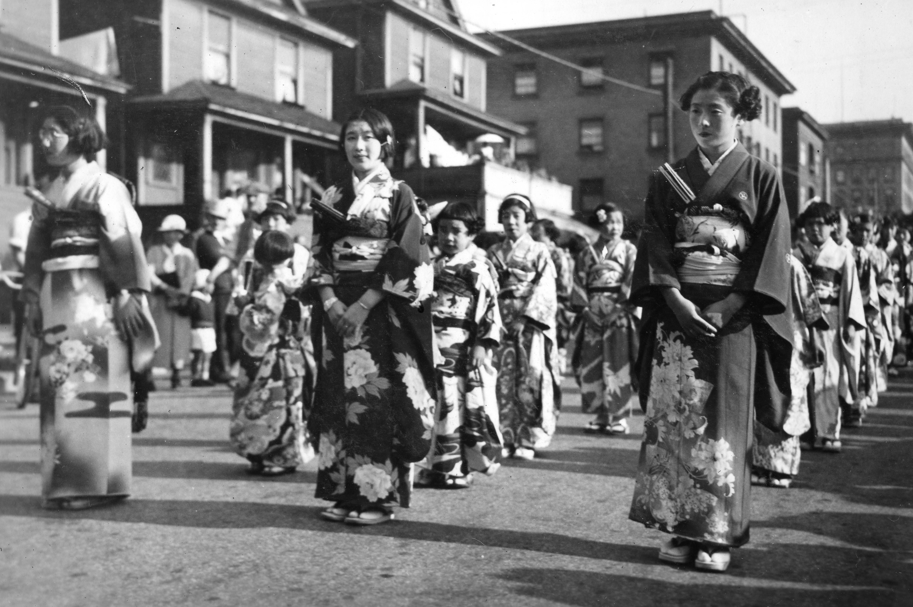 In this photo, three single-file lines of women in kimono march in the parade.