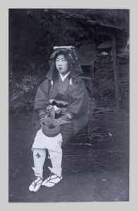 A glass negative copy of a commercial photograph of a Kyoto Oharame by John Cooper Robinson. A woman wearing sandals, kimono, and headdress sits upon a bundle of twigs.