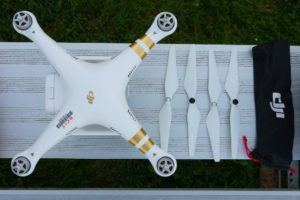 Photo showing the DJI Phantom 3 Professional drone from above with four propellers arranged next to it.