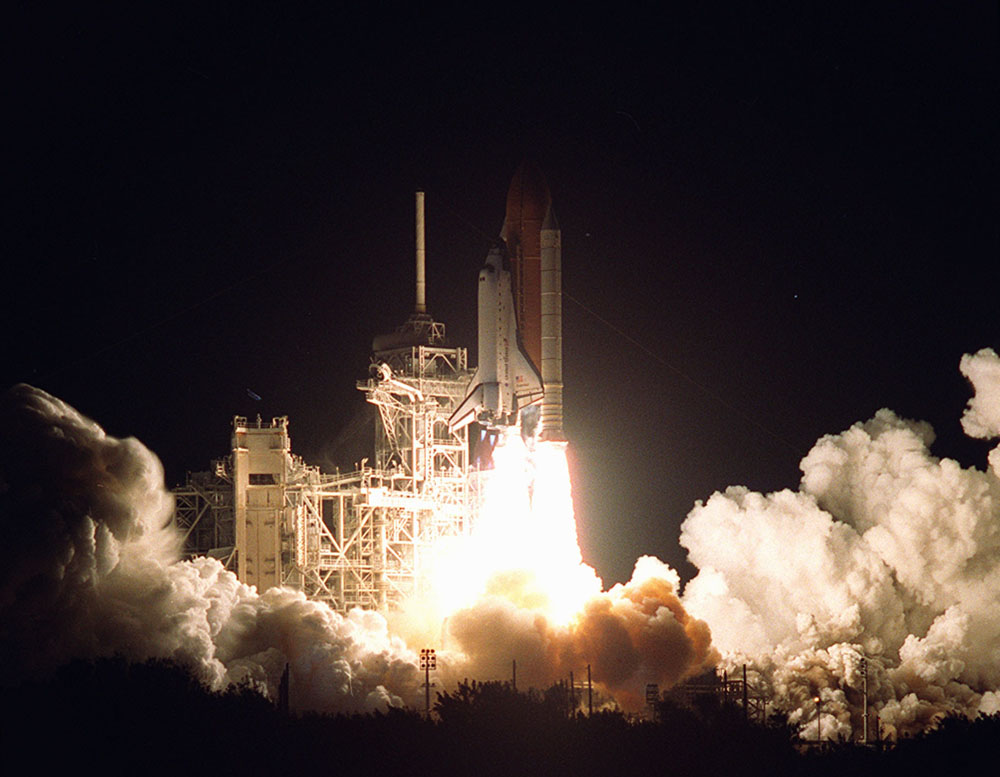 A space shuttle rocket is being launched and is burning propellant.