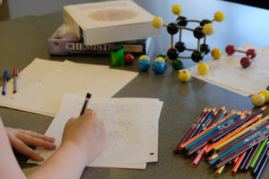 Student taking notes with pencils and chemistry models
