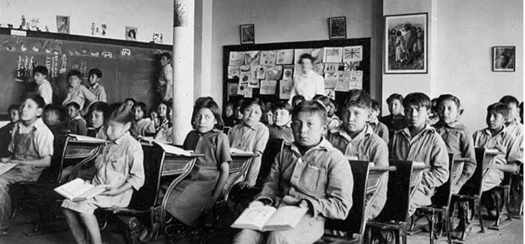 カナダのアルバータ州南部のOld Sun 英国国教会先住民学校。後ろの黒板の英国旗に注目。